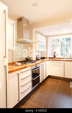 Modern white kitchen with wooden worktops and stainless steel appliances