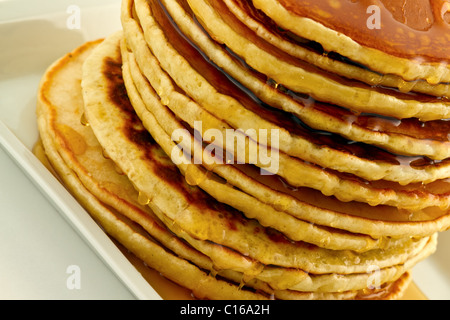 Stack of homemade pancakes with syrup on a white plate. - Stock Photo
