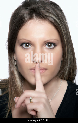 Young woman holding her index finger in front of her mouth asking for silence - Stock Photo