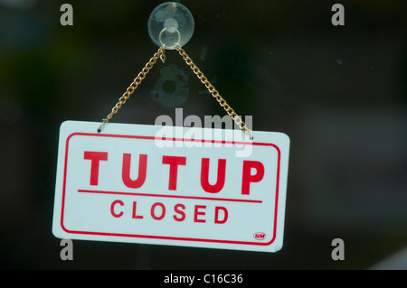 A sign in Indonesian saying 'Closed' - Stock Photo