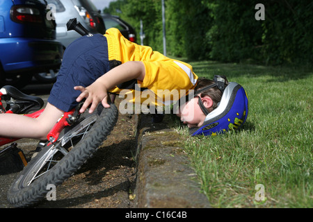 Five-year-old boy wearing a bicycle helmet falling off his bicycle, posed photo - Stock Photo