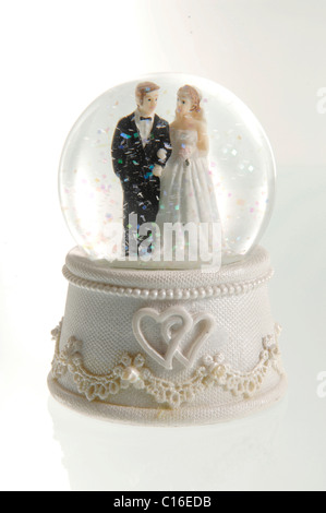 Porcelain bride and groom in a snow globe - Stock Photo