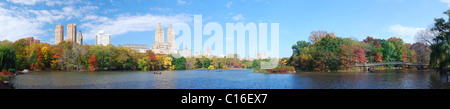 New York City Central Park panorama view in Autumn with Manhattan skyscrapers and colorful trees with Bow Bridge - Stock Photo