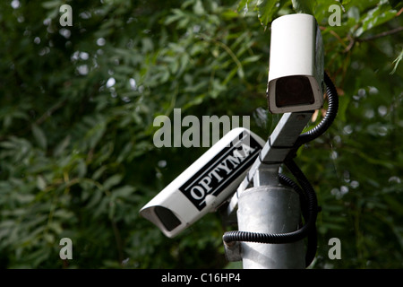 Two CCTV cameras pictured on the top of a pole in a garden in East Sussex, UK. - Stock Photo