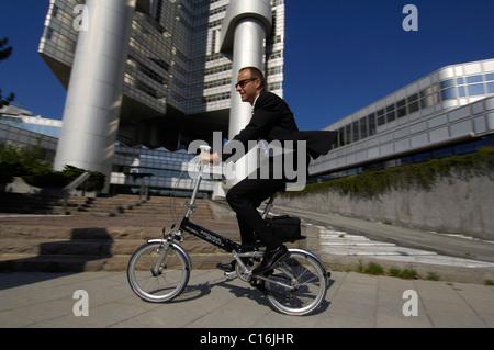 Businessman on his way to work on a folding bike, Hypobank building, Bogenhausen, Munich, Bavaria, Germany, Europe - Stock Photo