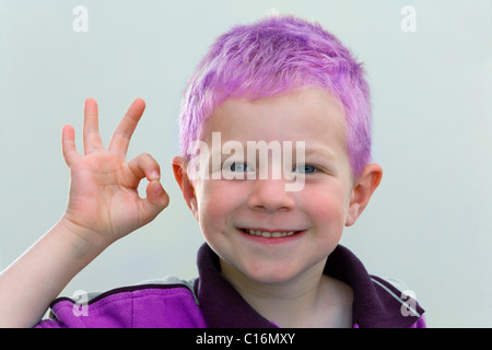 A four-year-old boy with purple hair wearing a purple sweater - Stock Photo