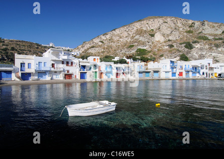 Sea and a fishing boat in front of colourful fishermen's houses in the fishing village of Klima, Milos, Cyclades, - Stock Photo