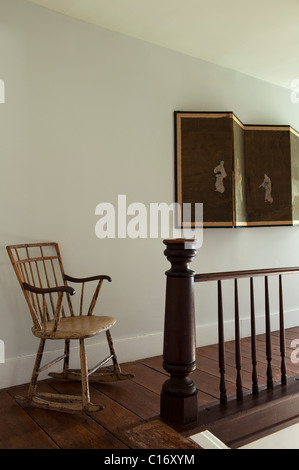 Rocking chair and Oriental folding screen on landing in 1830s Hudson Valley farmhouse, New York State - Stock Photo