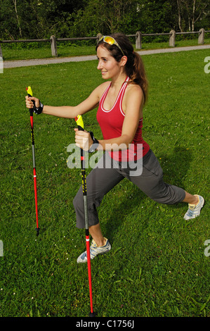 Woman doing stretching exercises with Nordic Walking poles, Allgaeu, Bavaria, Germany, Europe - Stock Photo