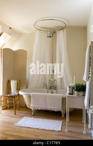 Roll-top bath in cream bathroom with cream curtains on window above ...