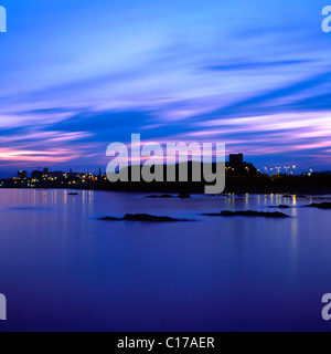 Mount Batten viewed from Jennycliff, Plymouth, Devon, England. A tower on a hill with distant city lights at sunset - Stock Photo