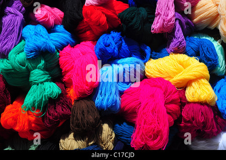 Collection of brightly coloured balls of wool on traditional market stall - Stock Photo