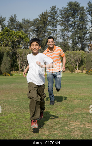 Man playing with his son in a park - Stock Photo