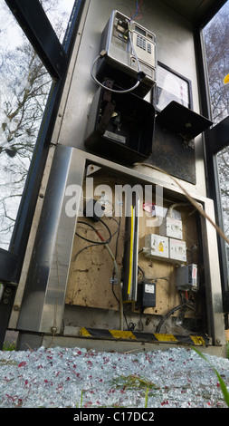A vandalised public telephone box. - Stock Photo