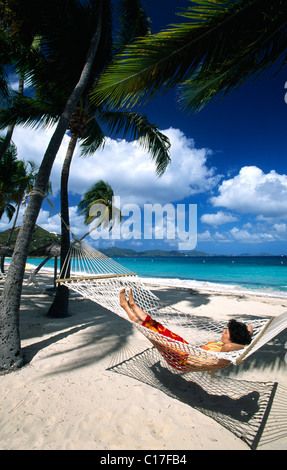 Woman in a hammock under palm trees on a beach on Peter Island, British Virgin Islands, Caribbean - Stock Photo