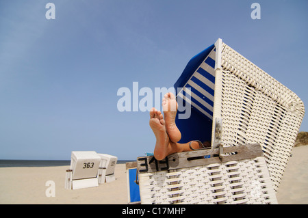 Feet resting on a roofed wicker beach chair near Wenningstedt, Sylt, North Frisian Island, North Sea, Schleswig - Stock Photo