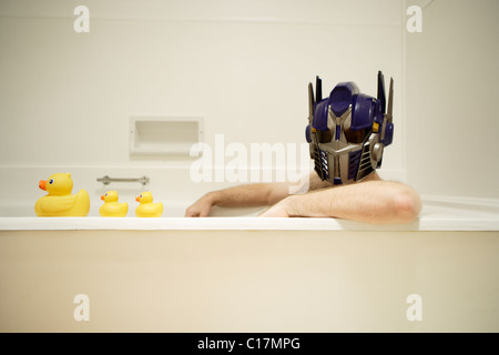Man wears toy helmet of the transformer robot Optimus Prime, a character in the Spielberg movie. - Stock Photo