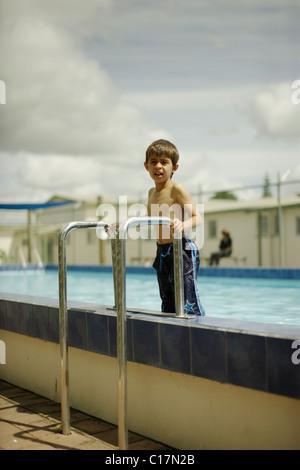 Six year old boy stands on steps as he gets out of the pool. - Stock Photo