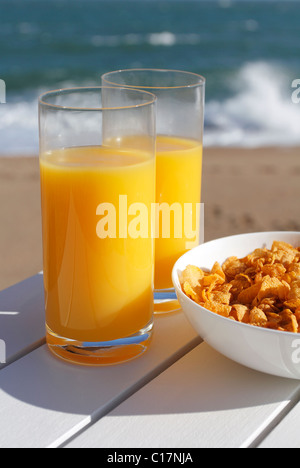 Glasses of orange juice and a bowl of cereal by the sea. - Stock Photo