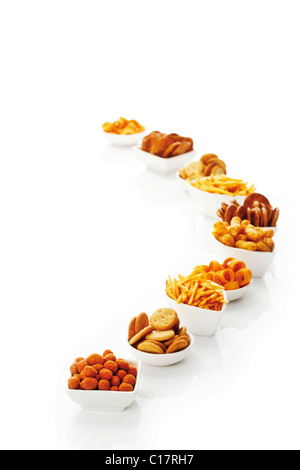 Assortment of spicy snacks, crispy sticks, salty biscuits, roasted peanuts, crispy rings and peanut flips in white - Stock Photo