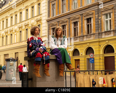 Medieval Festival in Sibiu, kids sitting on a gate pillar, of Evangelical Cathedral. - Stock Photo