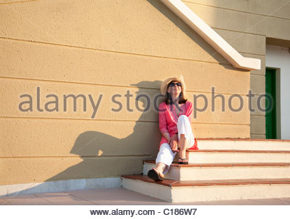 Woman relaxing in late afternoon sun - Stock Photo