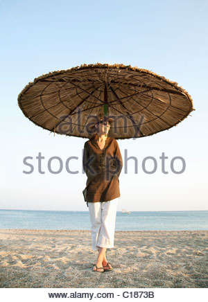 Woman on beach standing under parasol - Stock Photo