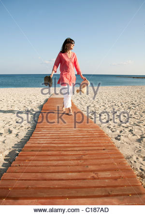 Woman walking on boardwalk on beach - Stock Photo