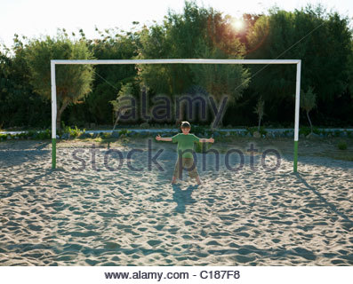 Boy (7-9) standing in soccer goal - Stock Photo