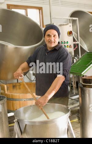 Worker producing bison mozzarella - Stock Photo