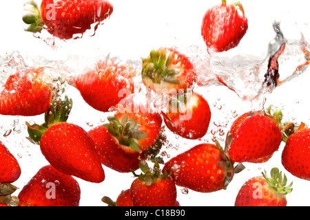 Photo of strawberries falling into water against a white background.Motion blur.