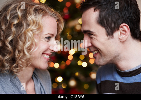Couple in front of xmas tree - Stock Photo