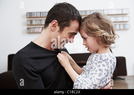 Girl buttoning up fathers shirt - Stock Photo