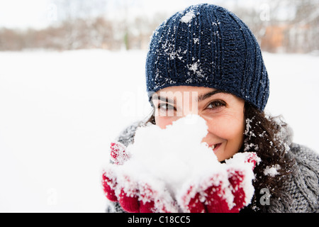Woman holding snow in hands - Stock Photo