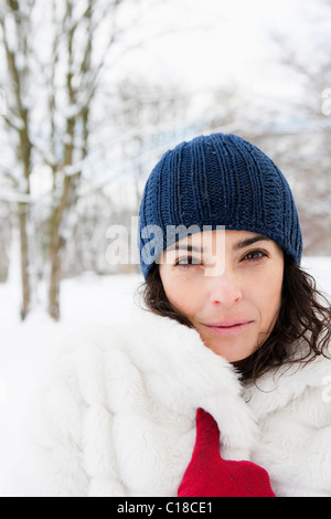 Woman in snowy woods looking to camera - Stock Photo