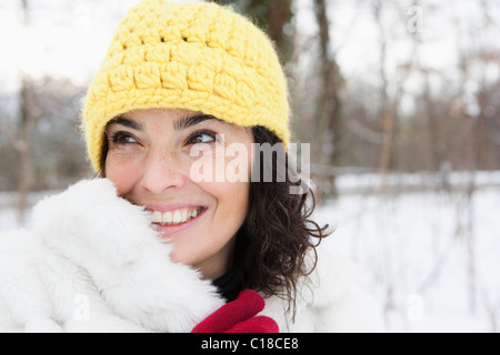 Woman in snowy woods wearing yellow cap - Stock Photo