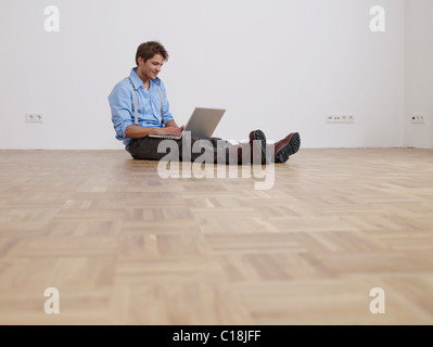Young man with laptop in empty flat - Stock Photo