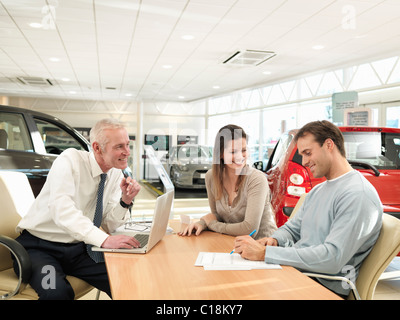 Salesman and customers in car dealership - Stock Photo