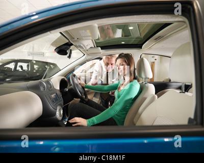 Salesman shows customer a car - Stock Photo