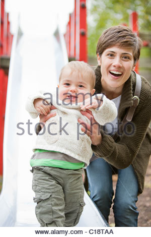 Woman and child play on slide in a park - Stock Photo