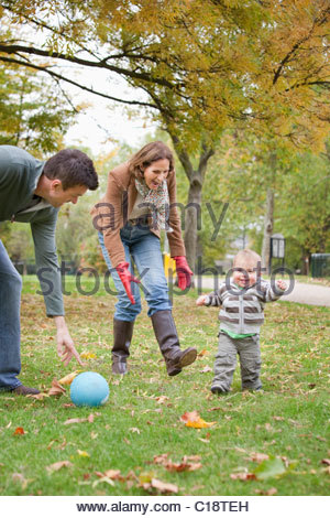 Family play soccer in the park - Stock Photo