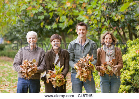 Family holding a bunch of leaves in park - Stock Photo