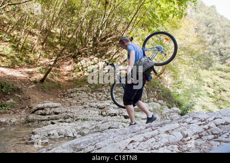 Man crossing a stream with bike - Stock Photo