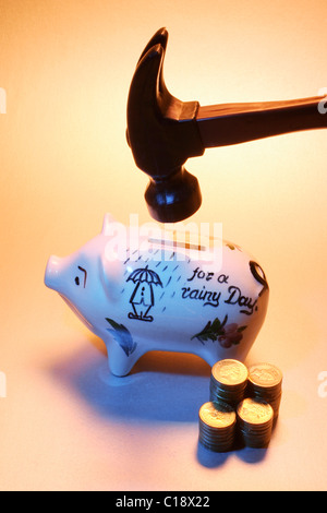 Coins and piggybank about to be smashed by hammer - Stock Photo