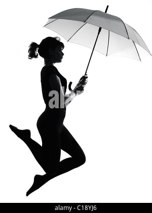 full length silhouette in shadow of a young woman flying with open umbrella  in studio on white background isolated - Stock Photo