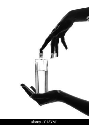 detail close-up silhouette in shadow of a  woman hands holding perfume in studio on white background isolated - Stock Photo