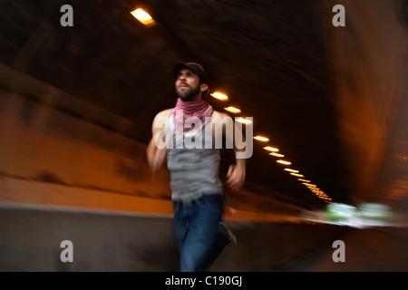 Man wearing Palastinien scarf running through a tunnel, Stuttgart, Baden-Wuerttemberg, Germany, Europe - Stock Photo