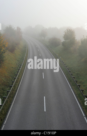 Foggy road in autumn - Stock Photo