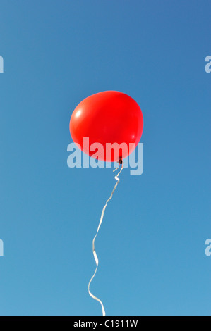 Red air balloon floating in blue sky - Stock Photo