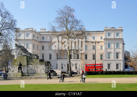 Exterior Neoclassical  Lanesborough Hotel 5 stars expensive luxury hotel with red London bus on blue sky day winter trees Hyde Park Corner London UK